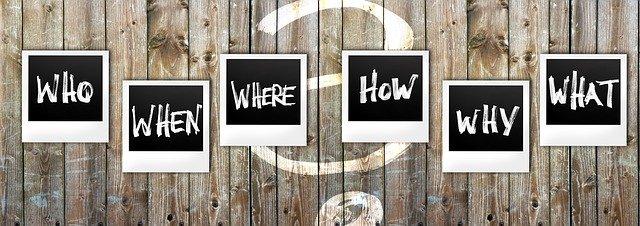 """nápisy na dřevených prknech """"kdy, kde, kam, kdo, jak, proč, co"""""""